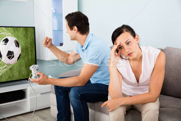 Woman Sitting Beside A Busy Man Addicted To Videogame Stock photo © AndreyPopov