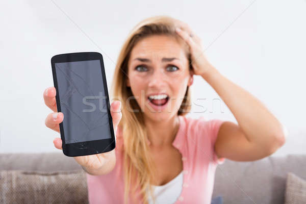 Stock photo: Shocked Woman Holding Damaged Phone