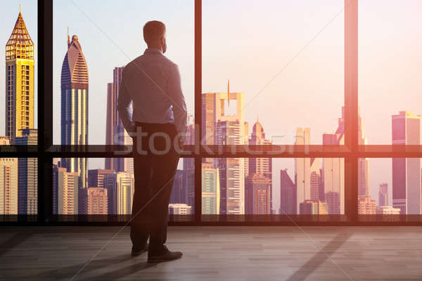 Businessman Looking At Cityscape Through Window Stock photo © AndreyPopov