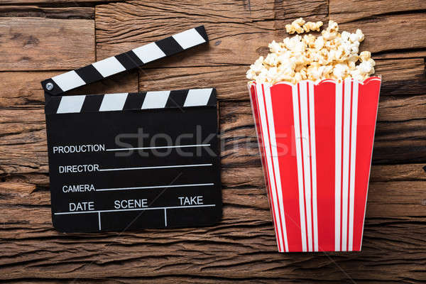 Clapperboard And Popcorn On Wood Representing Movie Time Stock photo © AndreyPopov