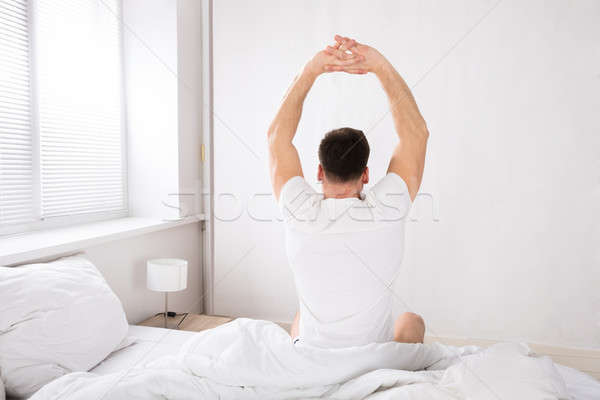 Man Stretch His Hand After Wake Up In Bed Stock photo © AndreyPopov