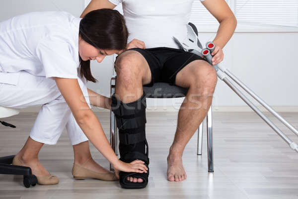 Female Doctor Putting Walking Brace On Person's Leg Stock photo © AndreyPopov