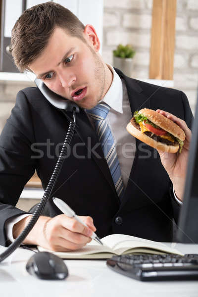 Business Man At Desk Eating Burger And Working Stock photo © AndreyPopov