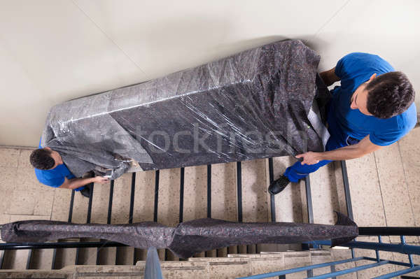 Stock photo: Two Movers Carrying Furniture On Staircase