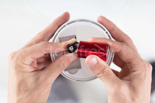 Person's Hand Inserting Battery In Smoke Detector Stock photo © AndreyPopov