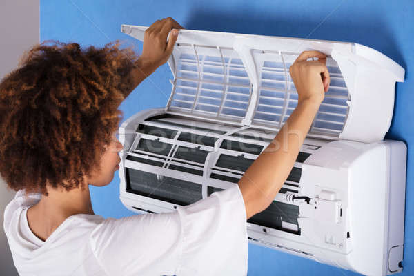 Woman Checking Air Conditioner At Home Stock photo © AndreyPopov