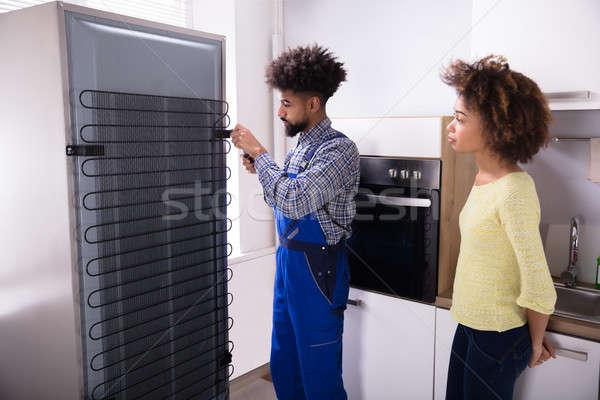 Teknisyen tamir buzdolabı mutfak kadın bakıyor Stok fotoğraf © AndreyPopov