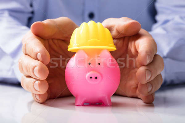 Person Protecting Hard Hat And Piggy Bank Stock photo © AndreyPopov