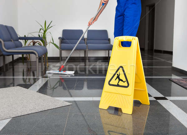 Stock photo: Man With Mop And Wet Floor Sign