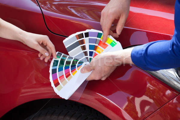 Mechanic Showing Color Samples To Customer Against Car Stock photo © AndreyPopov