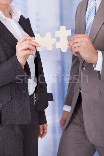 Stock photo: Business People Joining Jigsaw Pieces In Office