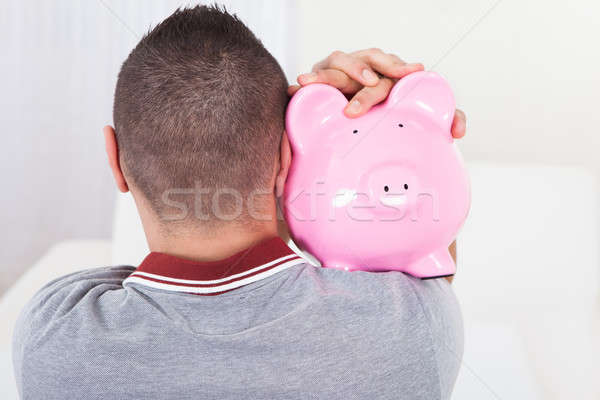 Man Holding Piggy Bank At Home Stock photo © AndreyPopov