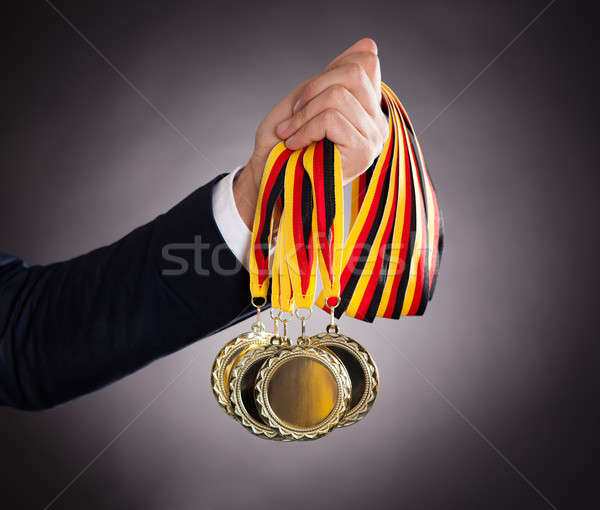 Businessman Holding Gold Medals Stock photo © AndreyPopov