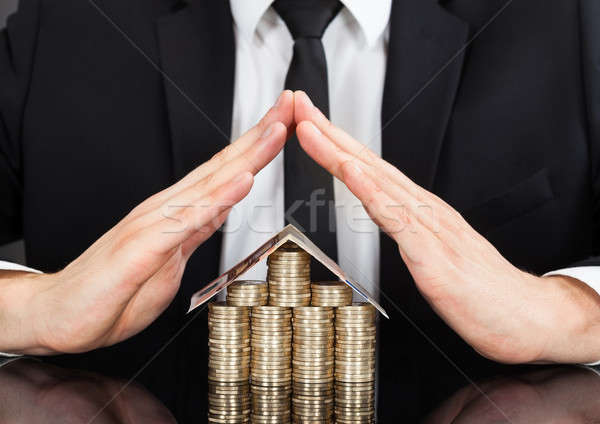 Businessman Shielding House Made Of Money At Desk Stock photo © AndreyPopov