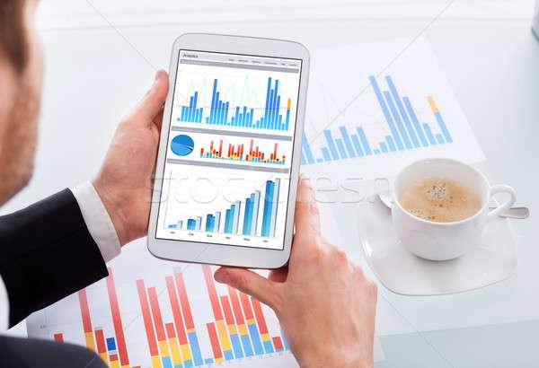 Businessman Comparing Graphs On Digital Tablet At Desk Stock photo © AndreyPopov