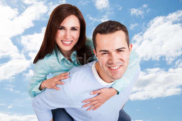Boldog férfi háton barátnő égbolt portré Stock fotó © AndreyPopov