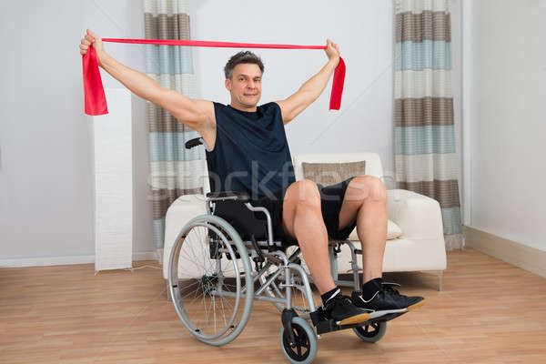 Handicapped Man On Wheelchair Exercising With Resistance Band Stock photo © AndreyPopov