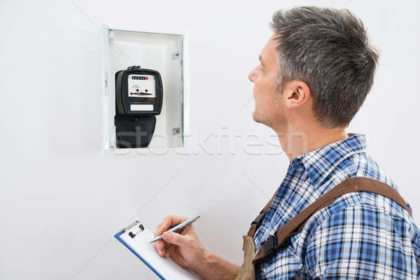 Technician Taking Reading Of Electric Meter Stock photo © AndreyPopov