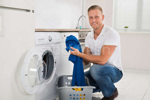 Stock photo: Man Loading Washing Machine With Clothes