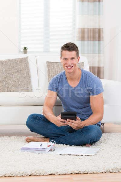 Homem orçamento calculadora moço sessão tapete Foto stock © AndreyPopov