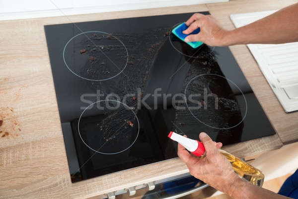 Janitor Cleaning Induction Stove In Kitchen Stock photo © AndreyPopov