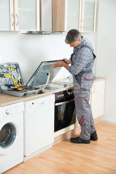 Repairman Examining Stove In Kitchen Stock photo © AndreyPopov