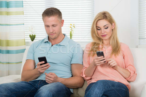 Couple Text Messaging Through Mobile Phones On Sofa Stock photo © AndreyPopov