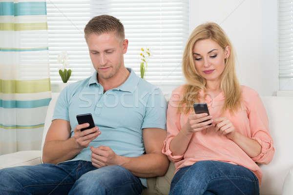 Paar mobiele telefoons sofa home Stockfoto © AndreyPopov