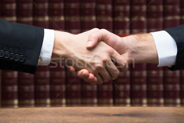 Judge And Client Shaking Hands Against Books Stock photo © AndreyPopov