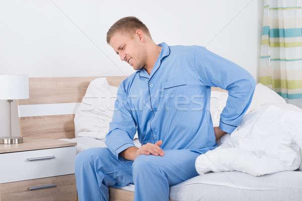 Férfi hátfájás ül ágy fiatalember szoba Stock fotó © AndreyPopov