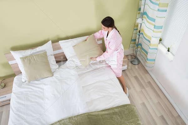 Female Housekeeper Arranging Bedsheet On Bed Stock photo © AndreyPopov
