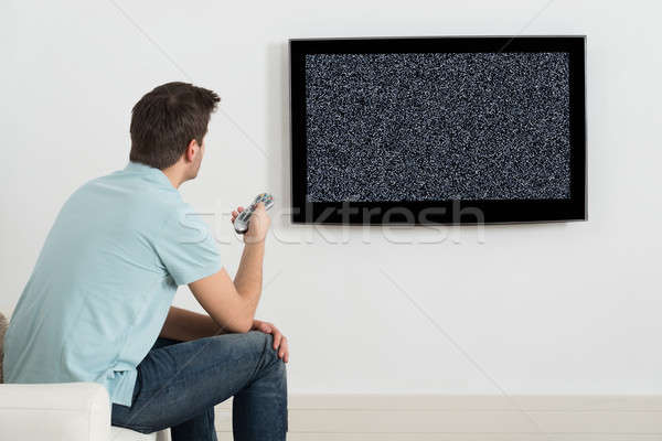 Man Sitting On Sofa In Front Of Television Stock photo © AndreyPopov