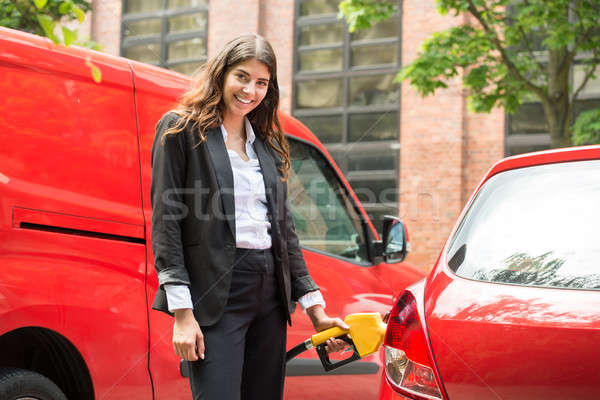 Businesswoman Refueling Car's Tank Stock photo © AndreyPopov
