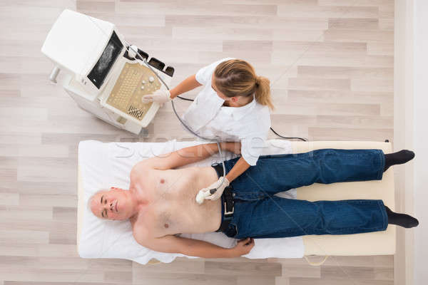 Doctor Using Ultrasound Scan On Abdomen Of Senior Male Patient Stock photo © AndreyPopov