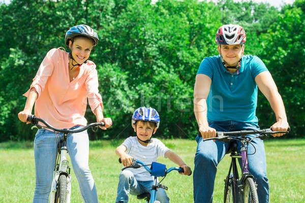 Boldog család biciklizik park portré mosolyog család Stock fotó © AndreyPopov