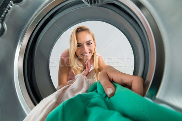 Woman Putting Clothes Inside The Washing Machine Stock photo © AndreyPopov
