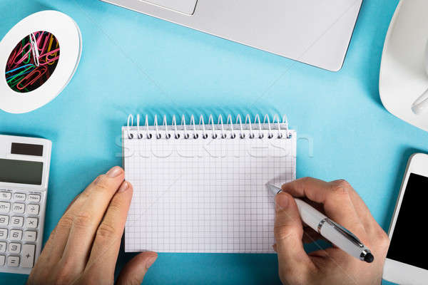 Businessman Writing On Checkered Spiral Notepad Stock photo © AndreyPopov