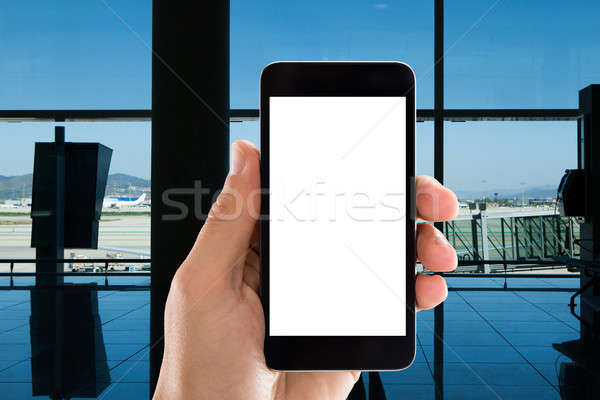 Hand Holding Mobile Phone With White Screen In Airport Stock photo © AndreyPopov