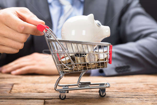 Businessman Pushing Piggybank And Coins In Shopping Cart Stock photo © AndreyPopov