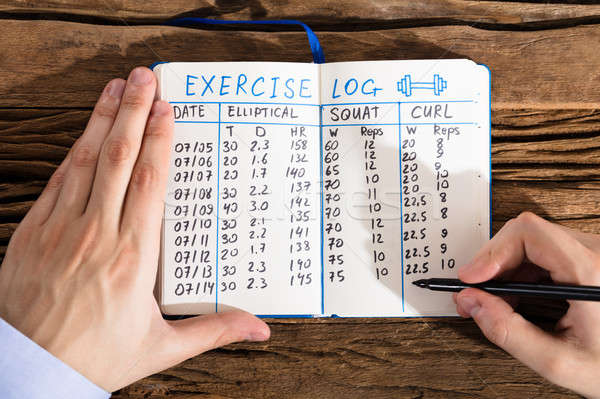 Person Filling Exercise Log On Notebook Stock photo © AndreyPopov
