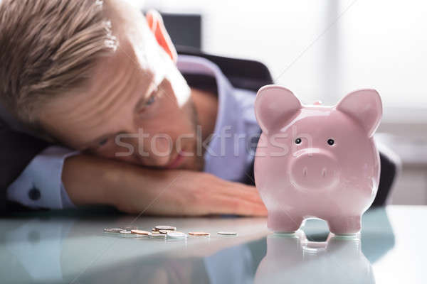 Depressed Man Looking At Coins And Piggybank Stock photo © AndreyPopov