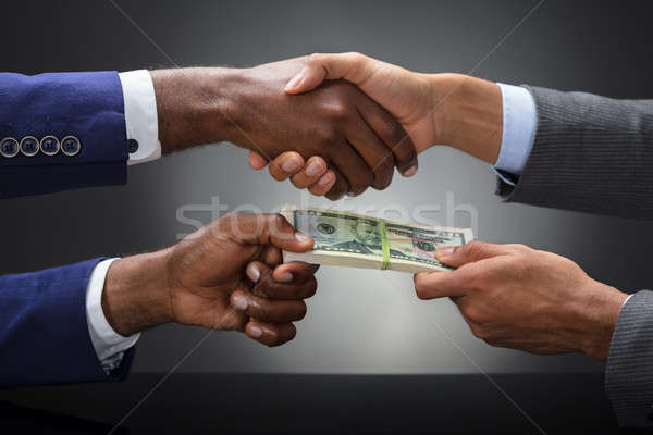 Businessman Shaking Hands While Bribing Partner Outdoors Stock photo © AndreyPopov