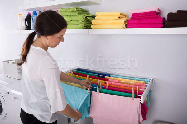 Woman Hanging Wet Clothes In Laundry Room Stock photo © AndreyPopov