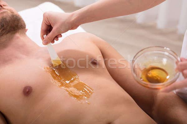 Beautician Applying Wax On Man's Chest Stock photo © AndreyPopov