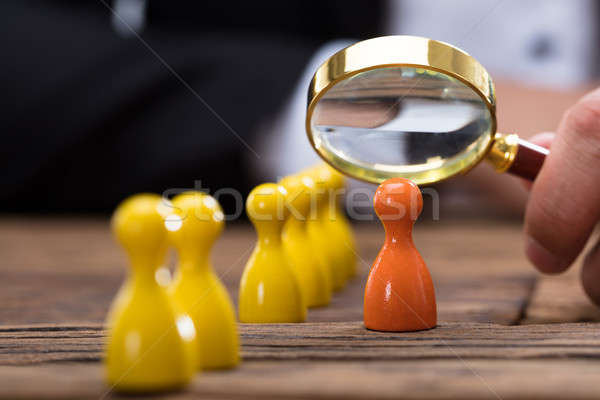 Businessperson holding magnifying glass over orange pawn Stock photo © AndreyPopov