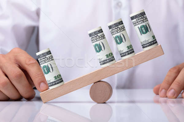 Human Hand Showing Unbalance Between Banknotes Stock photo © AndreyPopov