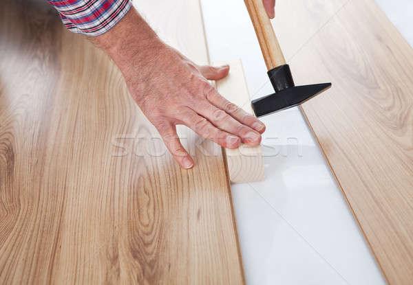 Stock photo: Worker assembling laminate floor