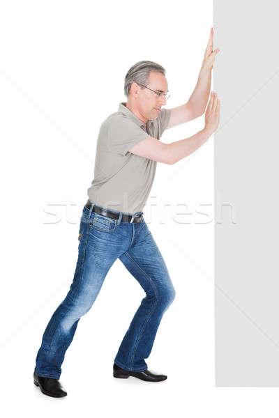 Portrait of mature man pushing placard Stock photo © AndreyPopov