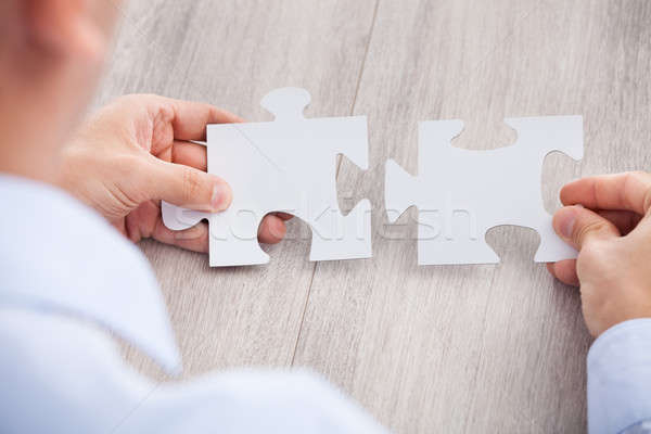 Cropped Image Of Businessman Joining Jigsaw Pieces Stock photo © AndreyPopov