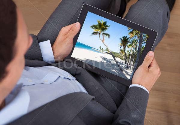 Stock fotó: üzletember · néz · tengerpart · fotó · tabletta · iroda